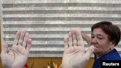 Босния-Герцеговина. Сараево шаарындагы кыргындын 15 жылдыгында маркумдардын аты чегилген дубалдын алдында дуба кылып жаткан аялдын колу. 28-август, 2010