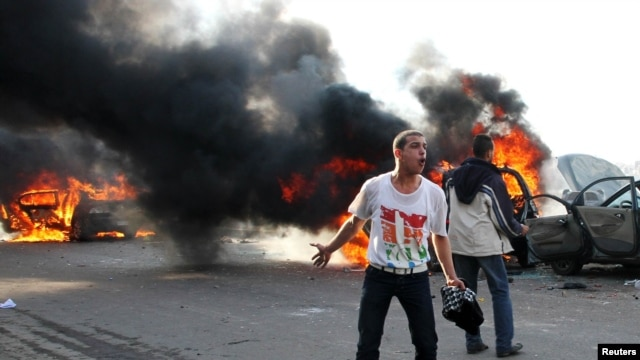 Antigovernment protester shouts slogans in front of burning cars during clashes with pro-government supporters in Alexandria on December 14.