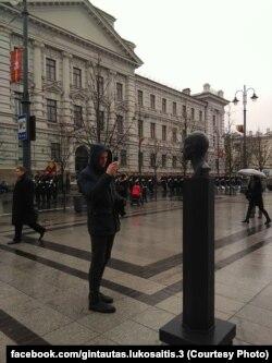Прохожий фотографирует памятник Павленскому, установленный напротив бывшего здания КГБ Литовской ССР