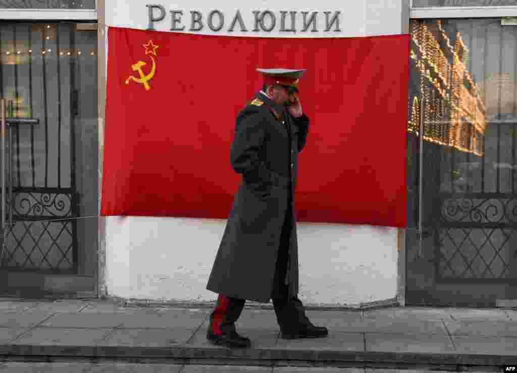 An impersonator of Soviet leader Josef Stalin walks past a hammer-and-sickle red flag in central Moscow on November 21. (AFP/Vasily Maximov)