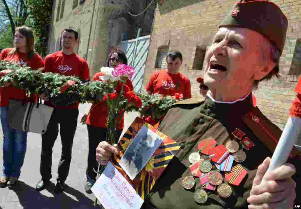 A Ukrainian WWII veteran wearing a Soviet-era uniform sings in a Victory Day march in the center of Kyiv.
