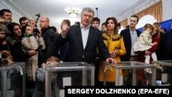 Діючий президент України і кандидат на президентських виборах Петро Порошенко разом із членами своєї родини на виборчій дільниці у Києві, 21 квітня 2019 року