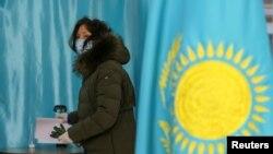 Женщина, голосующая на выборах в мажилис и маслихаты 10 января в Казахстане. Иллюстративное фото.