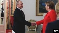 Russin President Vladimir Putin (left) and German Chancellor Angela Merkel shake hands during a bilateral meeting on the sidelines of the G20 in Buenos Aires.