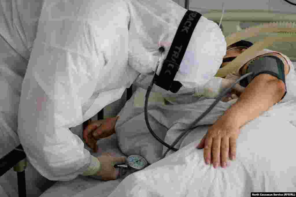 Врач проверяет давление пациента реанимации