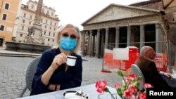 Një grua e veshur me një maskë mbrojtëse mban një filxhan në një restoran në Itali më 18 maj 2020.