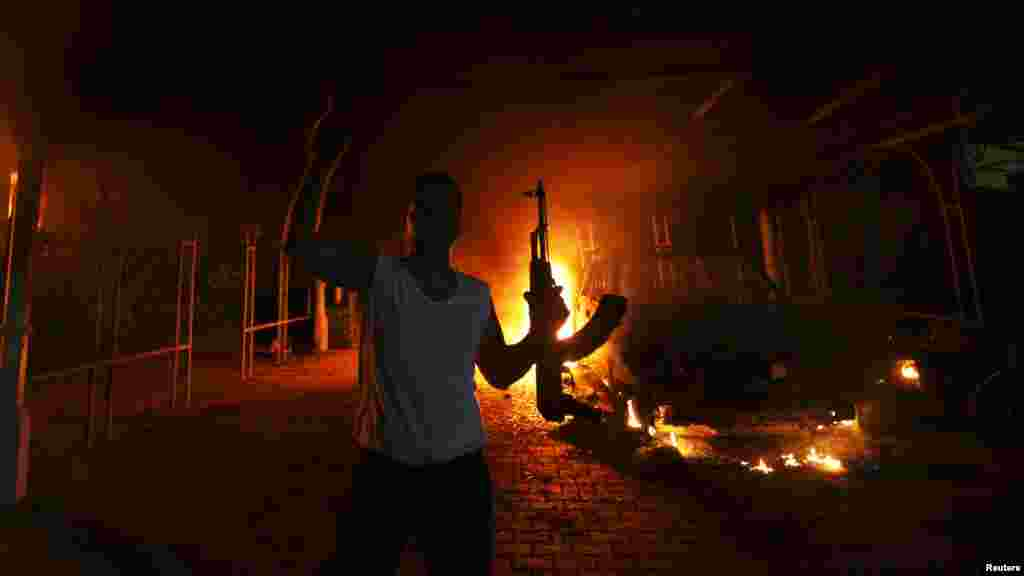 An armed man reacts as the U.S. Consulate in Benghazi, Libya, is seen in flames in an incident that killed U.S. Ambassador Chris Stevens and three other Americans. (Reuters/Esam al-Fetori)