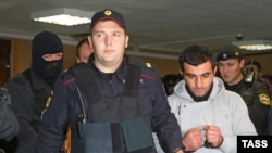 Orkhan Zeynalov (right) is escorted to a courtroom in Moscow on October 17.