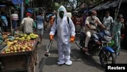 Специалист в защитной одежде во время санобработки в одном из городов Индии.