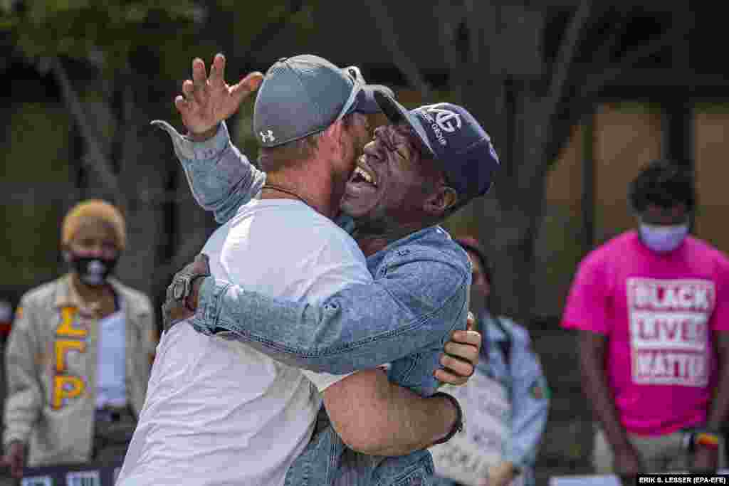 Black Lives Matter demonstrators Tim Higgins (Left) and Michael Jone (Right) embrace near Centennial Olympic Park in the wake of the Atlanta Police deadly shooting of Rayshard Brooks in Atlanta, Georgia, USA, 16 June 2020.