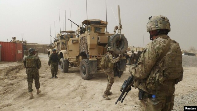 U.S. troops guard the entrance of the base in Kandahar Province where the accused U.S. soldier was serving.