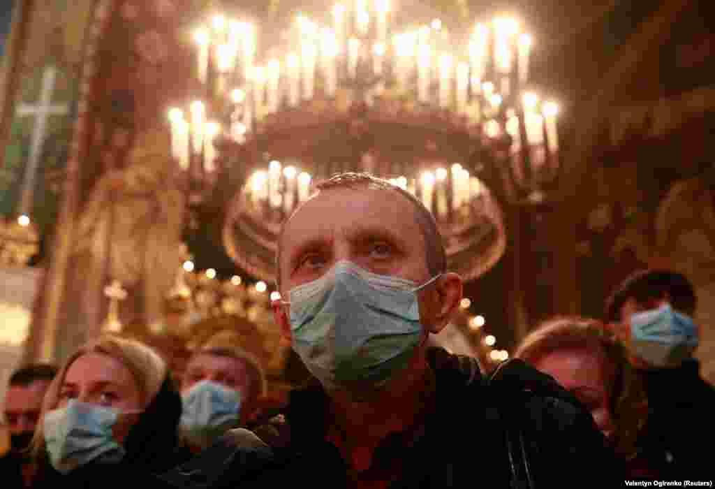 Besimtarët ke maska në fytyrë, marrin pjesë në meshën në Katedralen e Shën Volodimirit në Kiev.