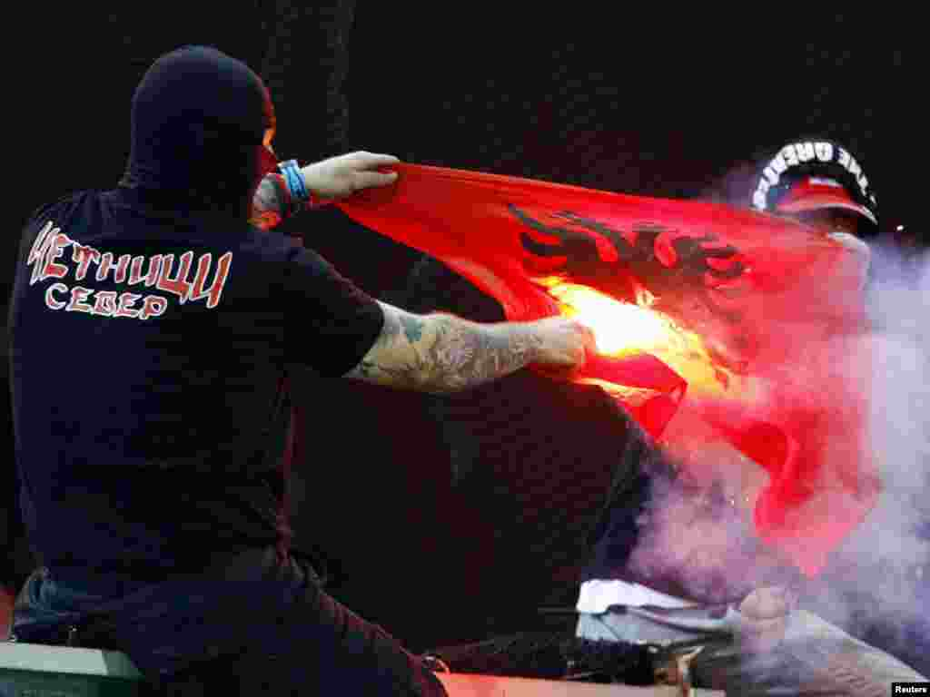 A supporter of Serbia's soccer team burns an Albanian flag before the Euro 2012 qualifying soccer match between Italy and Serbia in Genoa on October 12. The match was suspended after just six minutes and was likely to be abandoned when away fans threw flares onto the pitch and at Italian fans. Photo by Alessandro Garofalo for Reuters
