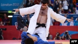 Russia's Mansur Isaev (white) celebrates after beating Japan's Riki Nakaya (blue) during their men's 73 kilogram judo contest final at the Olympic Games in London.