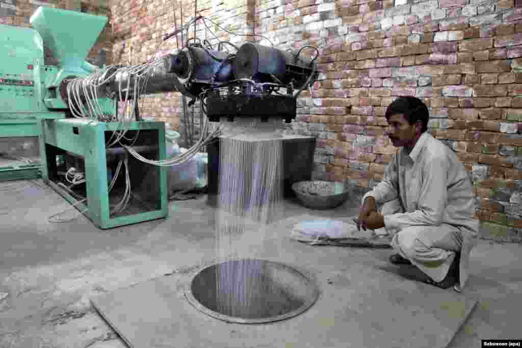 A worker watches as a machine spins out synthetic fibers.