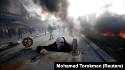 تصویری از درگیریها در کرانه باختری - یکی از فلسطینیان به این شکل پناه گرفته است