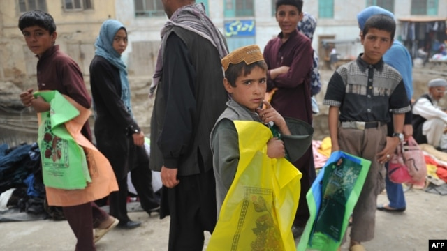 Afghan children sell plastic bags at a market in Kabul
