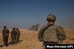 Американський військовий і солдат сирійських курдських сил спостерігають, як бульдозер знищує укріплення у «зоні безпеки» на кордоні з Туреччиною, 6 вересня 2019 року