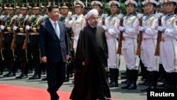 Iranian President Hassan Rohani (right) and Chinese President Xi Jinping review an honor guard during the welcome ceremony at the Xijiao State Guesthouse in Shanghai in May 2014.