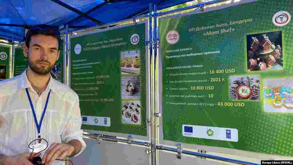 Un tânăr producător de dulciuri, la un stand care prezinta afacerea sa, inițiată cu susținerea Uniunii Europene