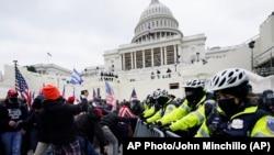 Поддржувачите на Трамп се обидуваат да ја пробијат полициската бариера во Кпитол во Вашингтон. 6 јануари 2021 година.