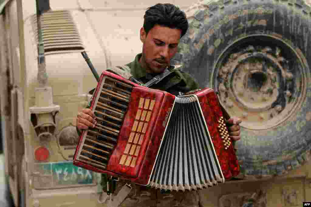 An Iraqi soldier plays with an accordion found on the street while on patrol in the western neighborhood of Tamuz in Mosul. (AFP/Ahmad al-Rubaye)