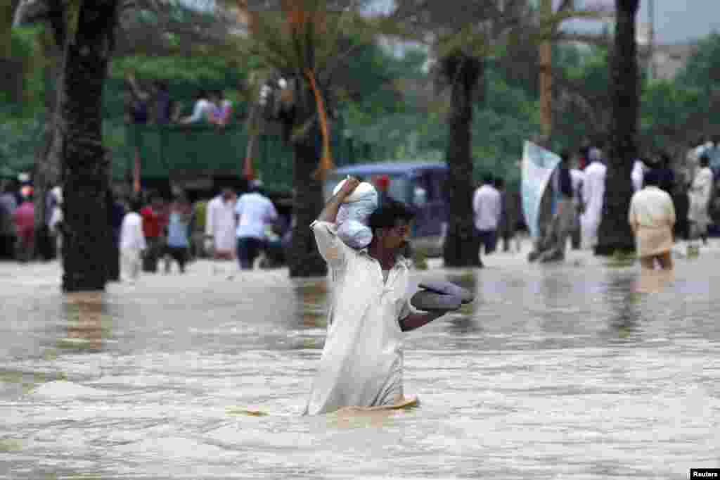 A man carries his belongings on his shoulder while wading through floodwaters outside of Karachi.