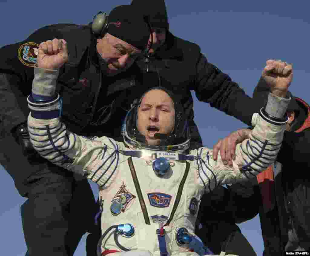 NASA astronaut Randy Bresnik is helped out of the Soyuz MS-05 spacecraft just minutes after it landed in a remote area near the town of Zhezkazgan, Kazakhstan, on December 14. Bresnik, Russian cosmonaut Sergei Ryazansky, and Paolo Nespoli of the European Space Agency spent 139 days in space. (epa-EFE/Bill Ingalls/ NASA handout)