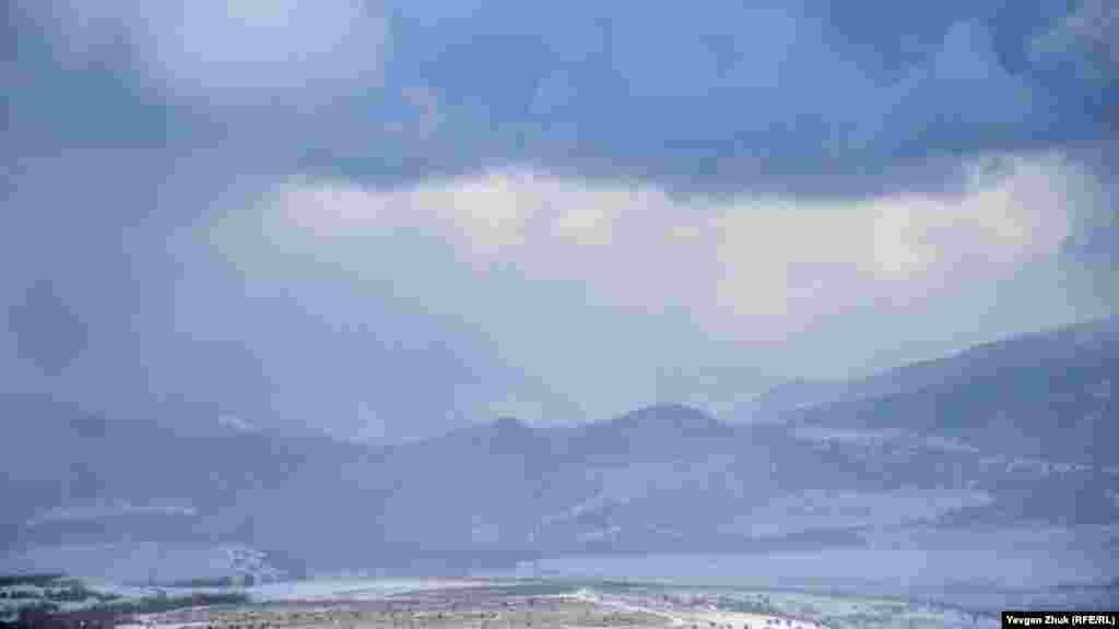 Краєвид з оглядового майданчика: в Балаклавській долині падає сніг, Кримські гори в далекій блакиті