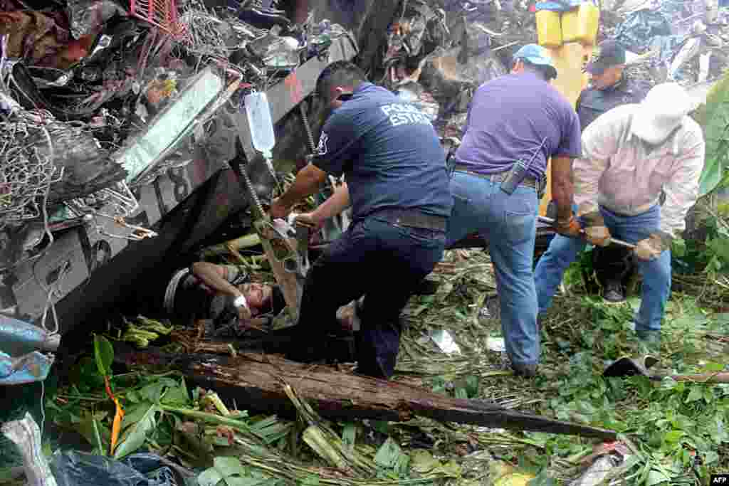 "Mexican state police officers help people trapped after a train, known as ""The Beast,"" derailed near Huimanguillo, Tabasco State, Mexico. The cargo train, which carries scrap metal and U.S.-bound migrants who pay smugglers for the right to sit atop freight cars, derailed in a swampy area of southeastern Mexico, killing at least six people. (AFP/""Tabasco Hoy"")"