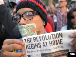 A man with a U.S. dollar bill taped over his mouth joins Occupy Wall Street protesters during a march to Foley Square in New York.