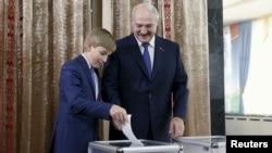 Беларусь президенті Александр Лукашенко ұлы Николаймен бірге дауыс беріп тұр. Минск, 11 қазан 2015 жыл.