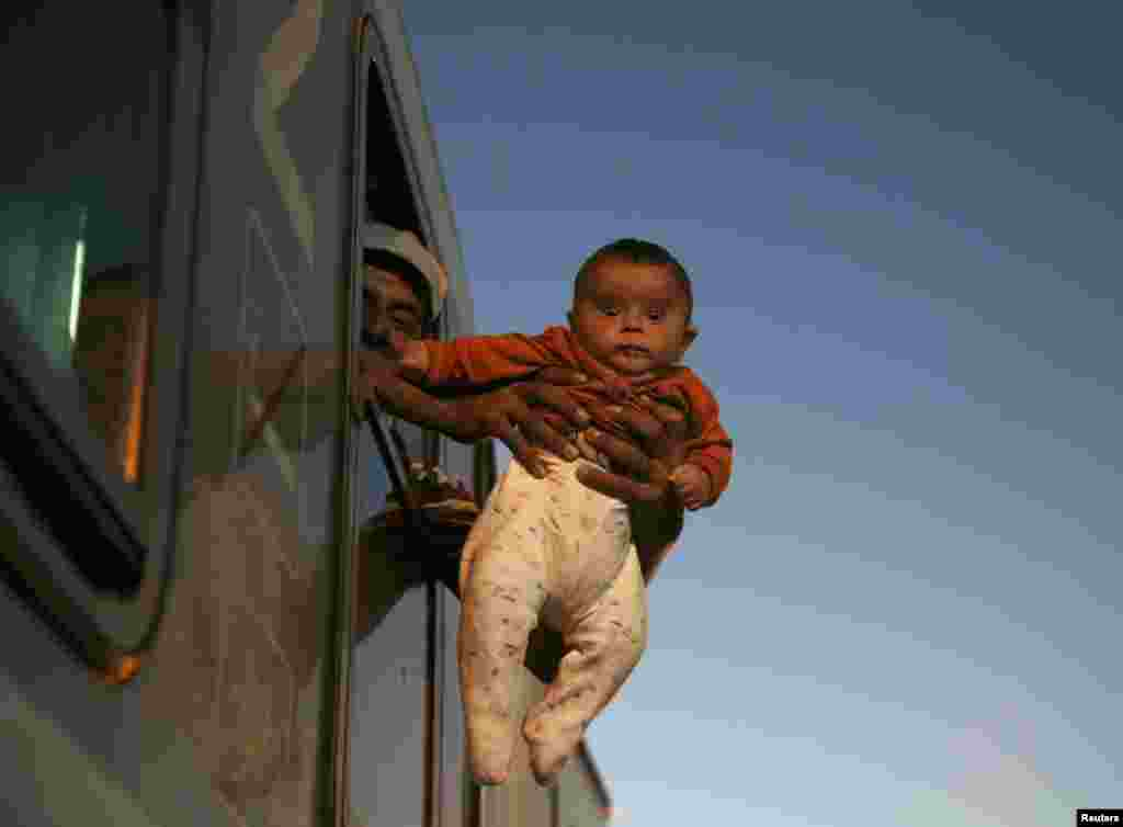 A migrant holds a baby outside the window of a train while waiting to depart from the railway station in Tovarnik, Croatia. (Reuters/Marko Djurica)