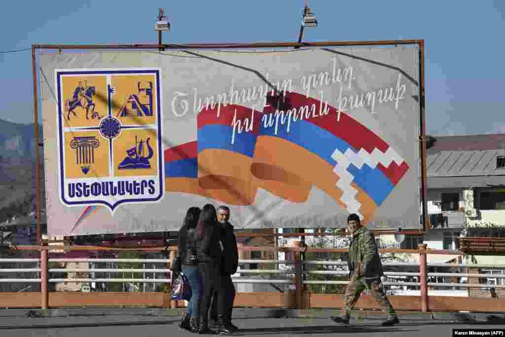 Местные жители идут мимо рекламного щита с сепаратистским флагом Нагорного Карабаха.