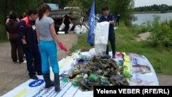 Активисты, откликнувшиеся на призыв акции по очистке малого озера в центральном парке Караганды, складируют собранный из озера и с прилегающей к нему территории мусор. Караганда, 30 июля 2016 года.