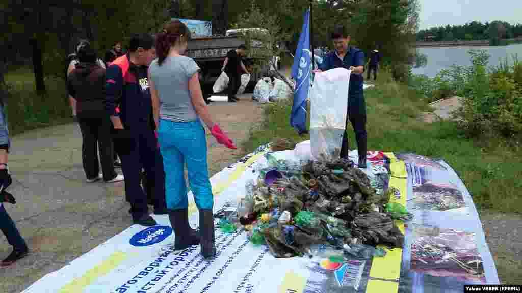 Активисты, откликнувшиеся на призыв акции по очистке малого озера в центральном парке Караганды, складируют собранный с озера и прилегающей к нему территории мусор.