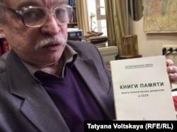 Анатолий Разумов с Книгой памяти