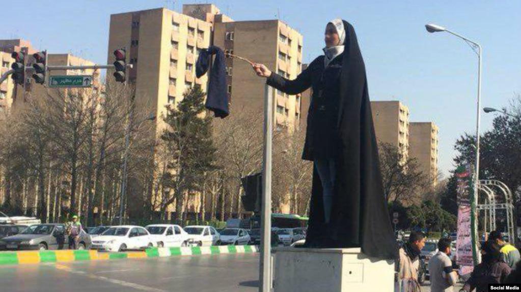 تصویر دختری چادری که در اعتراض به حجاب اجباری، روی یک چوب روسری آویزان کرده. گفته میشود این اقدام در مشهد صورت گرفته است.