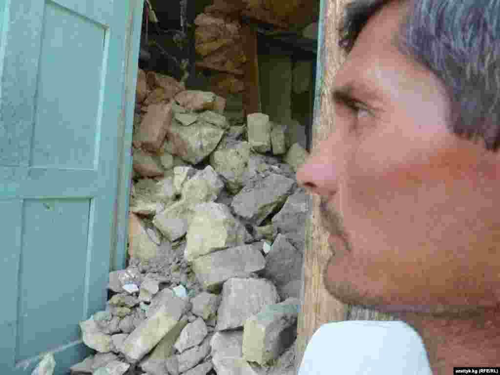 Кыргызстан: Баткен облусунун тургуну жер титирөөдөн кыйраган имараттын жанында. 21.7.2011.