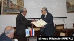 Predsjednik ANU RS Rajko Kuzmanović uručuje povelju počasnog člana predsjedniku Srpske akademije nauka i umjetnosti Vladimiru Kostiću