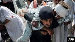 A security guard carries an injured blast victim as he arrives at a hospital in Peshawar.