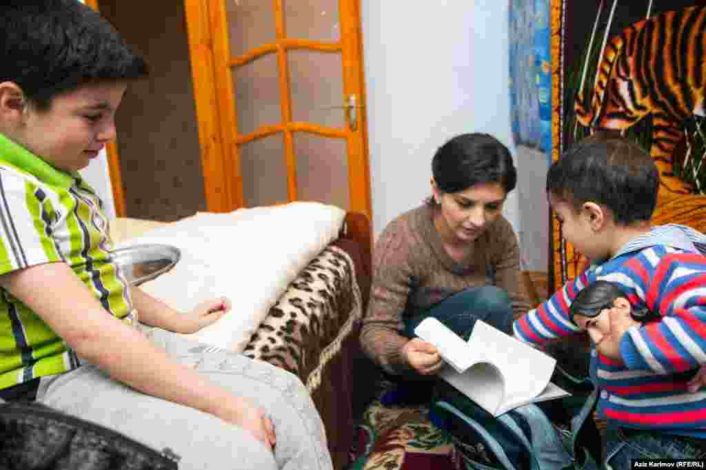 Rafiyeva with her two sons flipping through schoolbooks