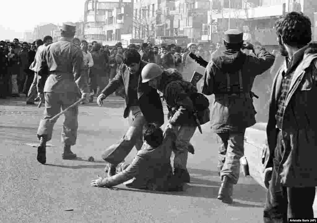 A demonstrator lifted from the ground by a soldier after being clubbed by a stick-wielding army officer (left) during a skirmish in Tehran on January 14, 1979.