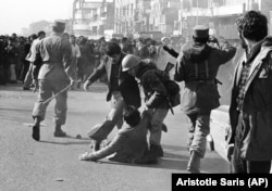 In this Jan. 14, 1979 file picture, a demonstrator is helped up from the ground by a soldier after being clubbed with a stick-weilding army officer, left, during a skirmish between demonstrators and the army in downtown in Tehran.