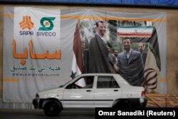 یک خودرو سایپا در حال عبور از مقابل تصویر بشار اسد و محمود احمدینژاد در حمص سوریه/ این تصویر در شهریور ۹۷ گرفته شده است