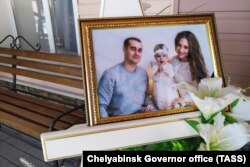 A photo of Igor, Milana, and Anastasia Kramarenko, who died in the collapse, is displayed before a farewell ceremony in Magnitogorsk on January 4.