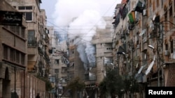 A man stands in an empty street near a burning building hit by a mortar shell fired by Syrian Army soldiers, in the Zamalka neighborhood of Damascus.