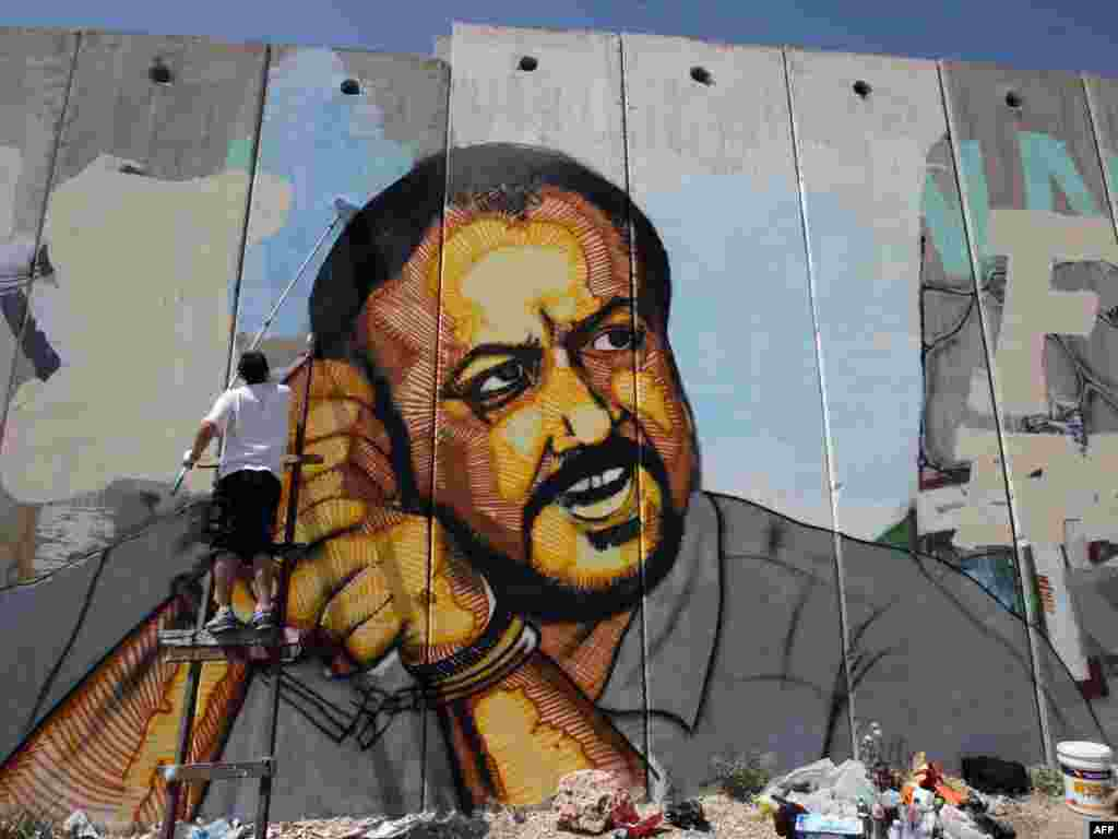 A Palestinian artist puts finishing touches on a portrait of jailed Fatah leader Marwan Barghuti on the cement barrier dividing the West Bank from Israel. Photo by Abbas Momani for AFP