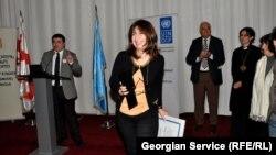"RFE/RL Tbilisi Bureau Chief Marina Vashakmadze (center) accepting the ""Champion of Tolerance"" award from Georgian Public Defender's Office head Beka Mindiashvili (left) during a ceremony in Tbilisi, 15Nov2012"