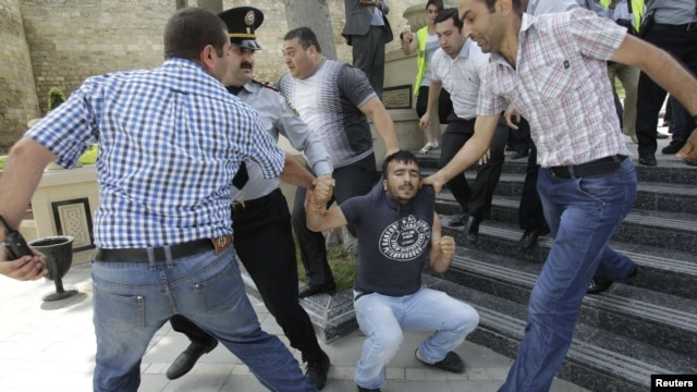 Azerbaijani plainclothes police officers detain an opposition supporter during an antigovernment protest in central Baku on May 21.